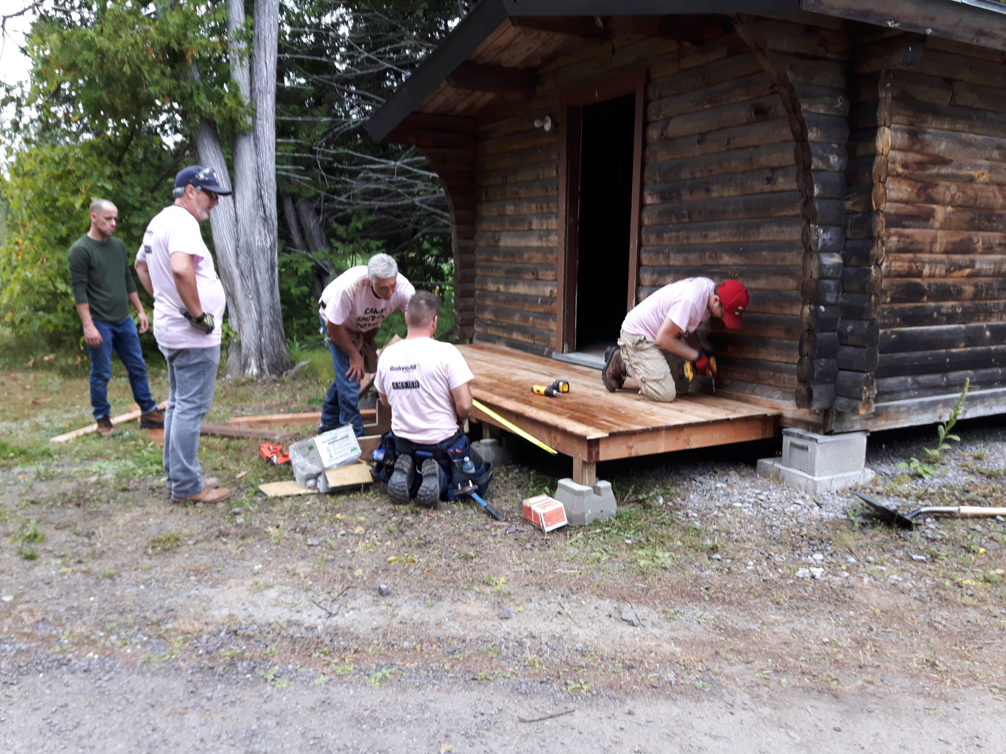 Photo of five people working on building a cabin