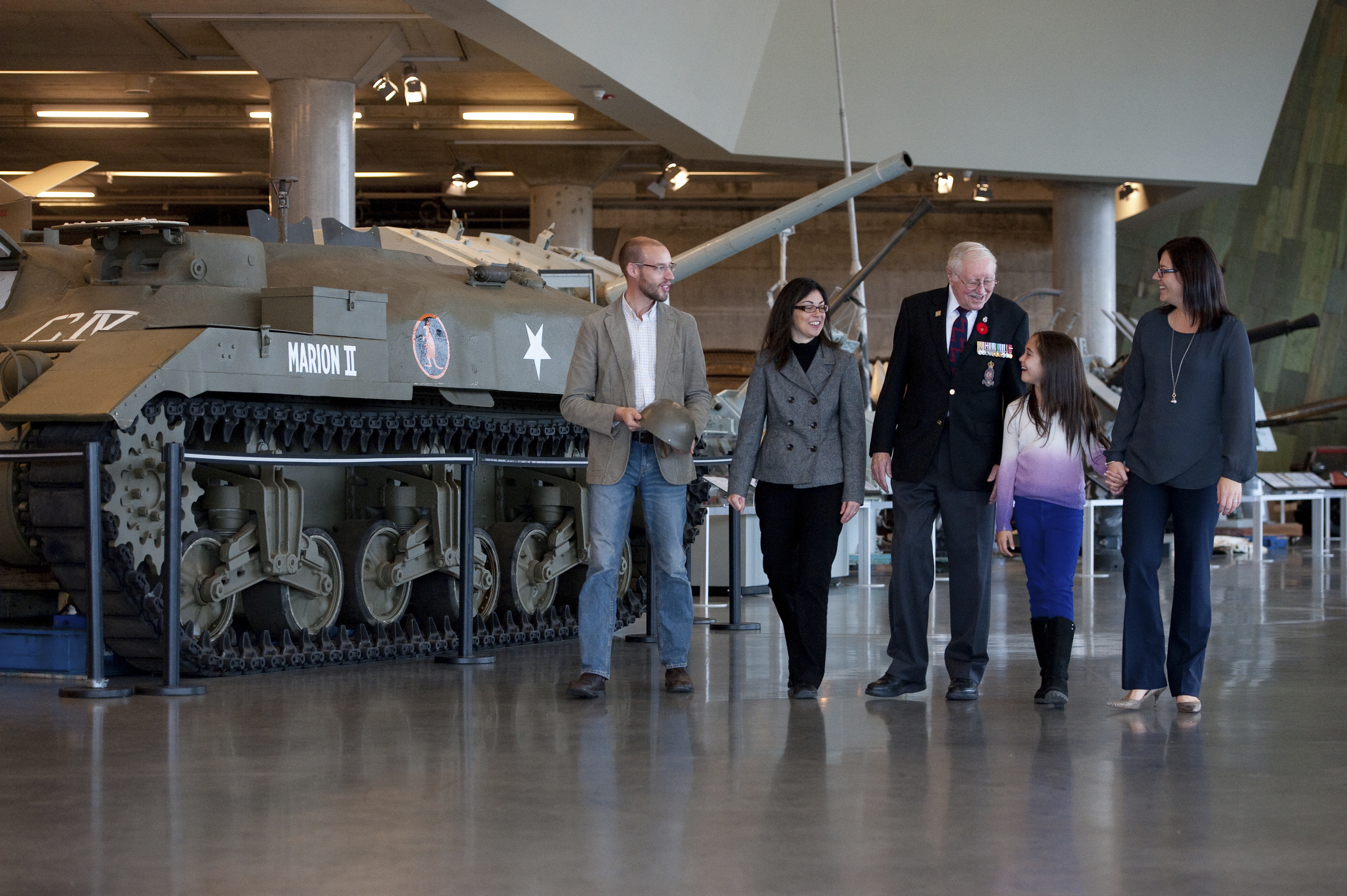 A veteran gives a family a tour of the LeBreton Gallery at the Canadian Ware Museum.