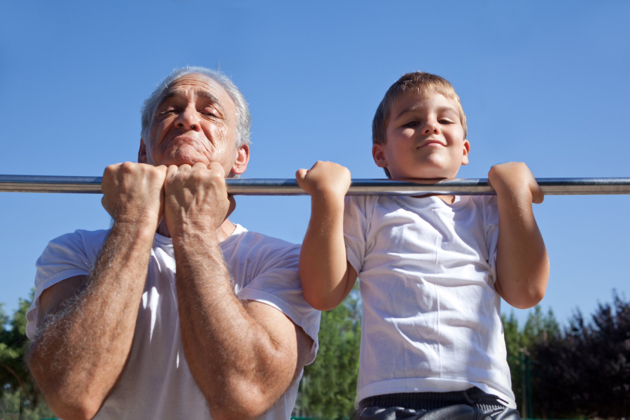 An image of an elderly man and a child doing chin ups.