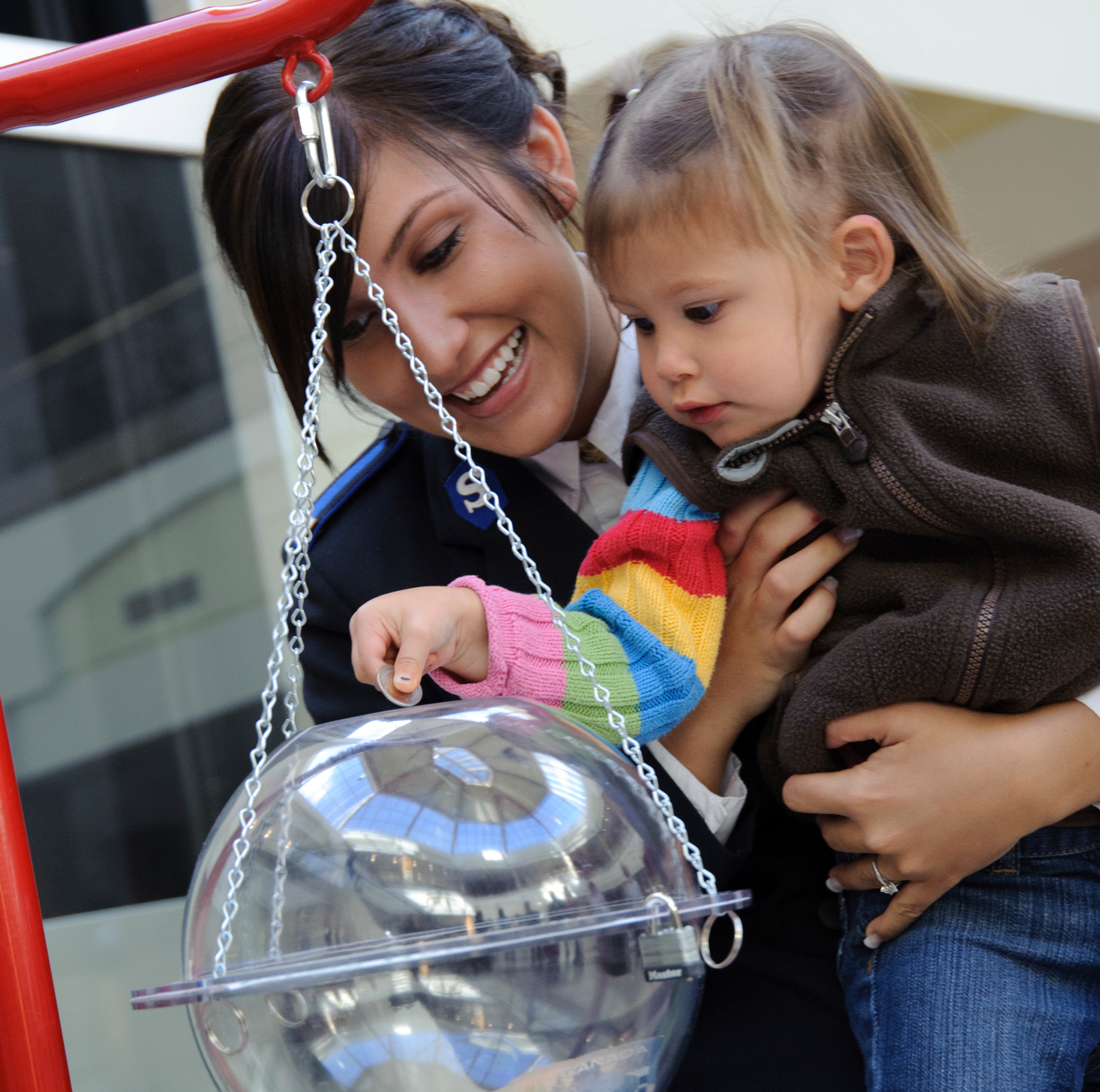Image of woman and child putting a coin into a christmas kettle