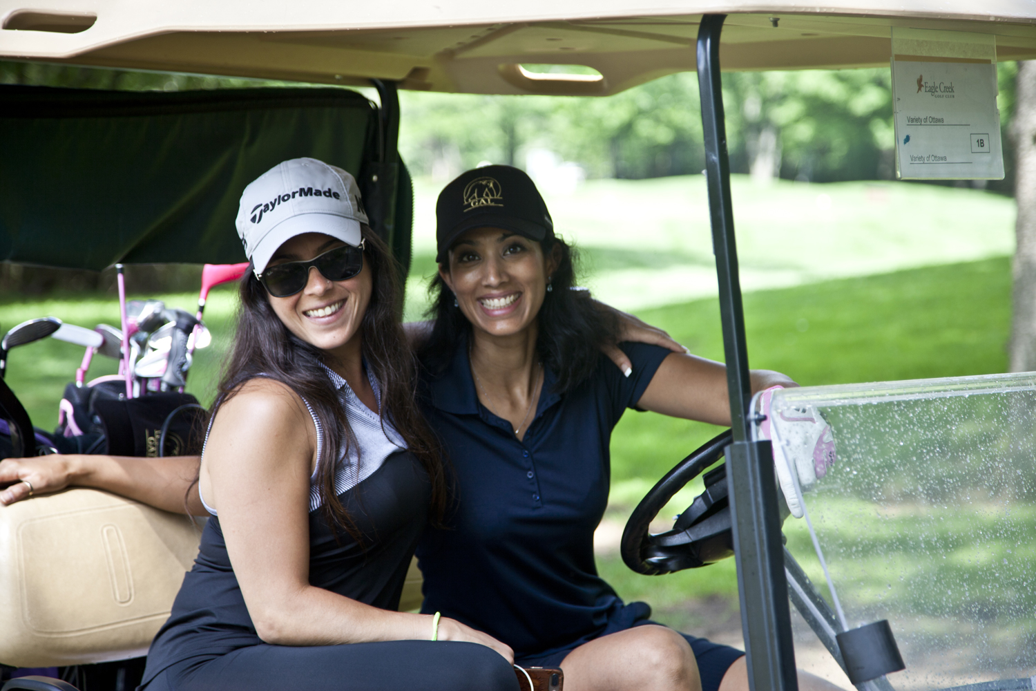 Two women in a golf cart, smiling.