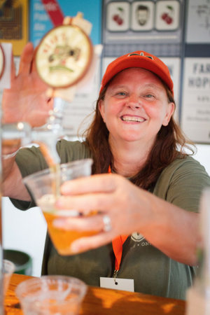 A woman serves a beer at Beau's Oktoberfest