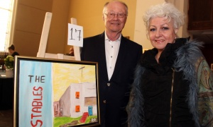 Operation Come Home board member Robin Ritchie, senior counsel at Perley-Robertson, Hill & McDougall, poses alongside his artwork and his wife, Ester Ritchie, at the Glebe Community Centre on Saturday, March 25, 2017, for the return of the Big Art Come Back fundraiser for Big Brothers Big Sisters of Ottawa and Operation Come Home. (Photo by Caroline Phillips)