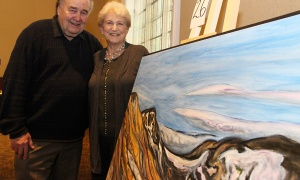 Visual artist Michael Sproule, from Chelsea, Que., and his wife, Mary, pose with his oil on canvas, Glacial Ablation, at the Glebe Community Centre on Saturday, March 25, 2017, for the return of the Big Art Come Back fundraiser for Big Brothers Big Sisters of Ottawa and Operation Come Home. (Photo by Caroline Phillips)