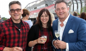 From left, Massage Addict clinic owners Larry Poirier and Lucille Perreault, in their Redblacks colours,  with retired police sergeant Dan Dunlop, a partner with Inquisit Solutions, at a benefit for CHEO's IBD Centre held at Ottawa Redblacks president Jeff Hunt's condo overlooking the football team's opening home game on Friday, June 23, 2017. (Photo by Caroline Phillips)