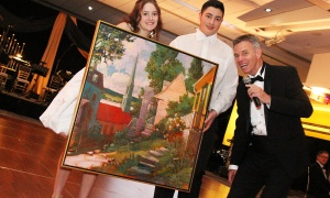 Starr Brommell, a student at Glebe Collegiate, and Zach Ajaj, a student at St. Francis Xavier Catholic High School, hold up a Philip Craig painting that was sold off by Michael O'Byrne at the Viennese Winter Ball. Photo by Caroline Phillips