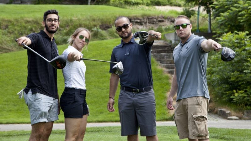 Four golf players pose with their clubs.