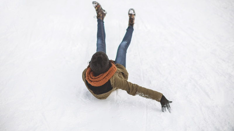 A woman slips and falls on ice