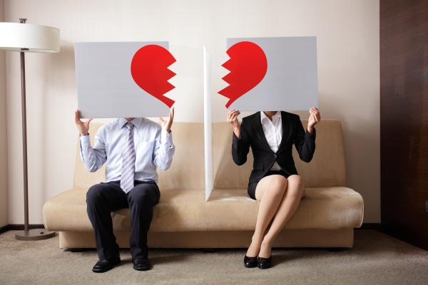 Two people sit on a couch, holding signs with the two sides of a broken heart over their faces.