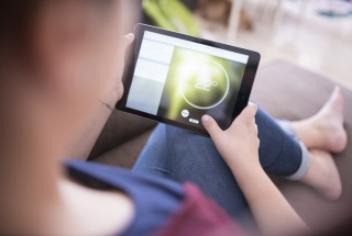 A woman holding a tablet with a smart home software open on it.