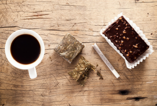 An overhead shot of a table, with a coffee, some hash, a joint and a brownie on it