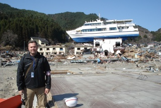 Ioan Nistor in Japan, posing in front of a boat brought ashore by the tsunami.